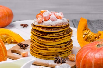 A stack of homemade pumpkin punkcakes with powdered sugar on top and candied kumquat.