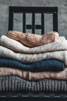 회색 벽 옆 의자에 따뜻하고 아늑한 니트 스웨터 더미. 가을, 겨울 개념.