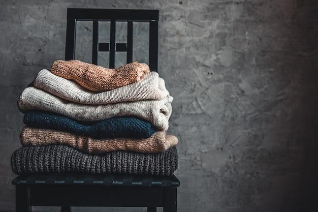 Пачка вязаного теплого уютного свитера на стуле у серой стены