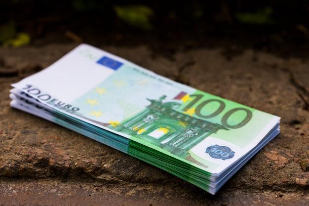 돌계단 위에 100유로의 돈 더미가 놓여 있습니다. 고품질 사진