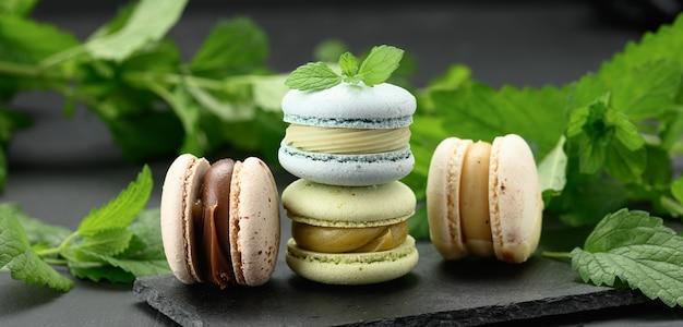 Стопка разноцветных макарон на черной поверхности, за зелеными веточками мяты, вкусный и изысканный десерт, баннер