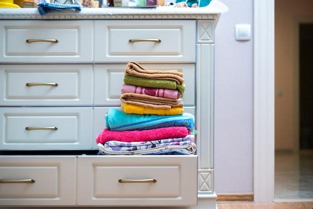 洗濯物の棚に新しい清潔で新鮮な色のタオルテキスタイルのスタック