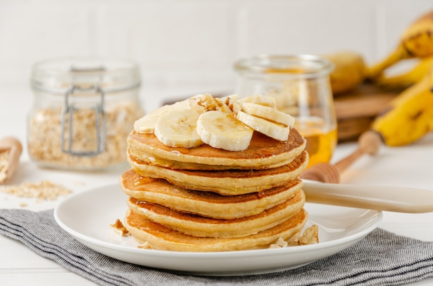 新鮮なバナナ、クルミ、蜂蜜のスライスと白い木製の背景にお茶のカップとオートミールバナナのパンケーキのスタック。健康的な朝食。スペースをコピーします。