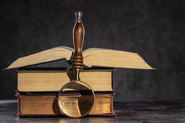 어두운 배경과 돋보기 위에 탁자 위에 놓여 있는 오래된 책 더미.