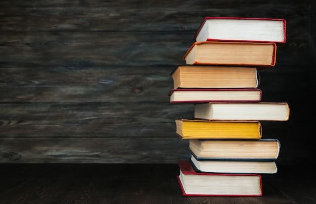 Стог старых книг на деревянном космосе экземпляра предпосылки.