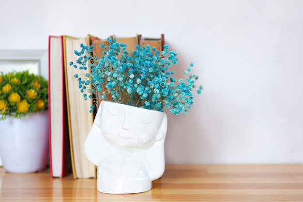꽃의 화병과 함께 오래 된 책의 스택입니다. 복사 공간입니다.