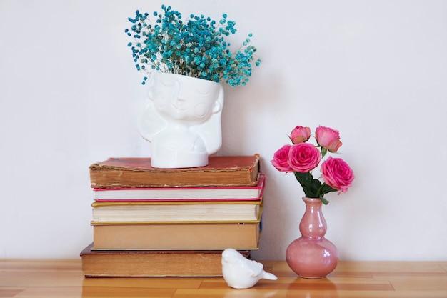 꽃의 화병과 함께 오래 된 책의 스택입니다.