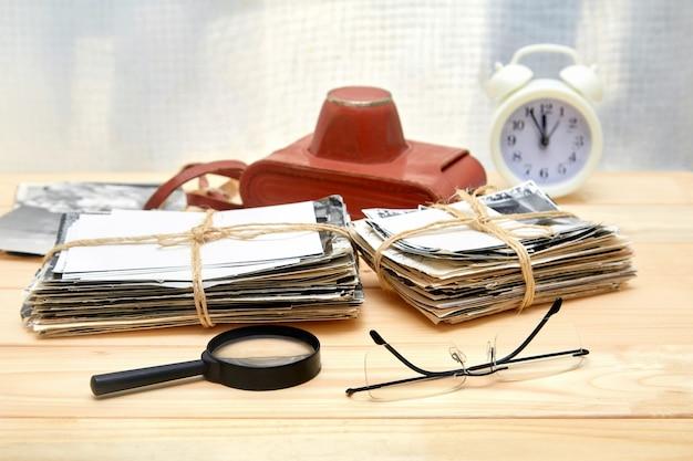 Стопка старых фотографий, очки, лупа и будильник на деревянном столе