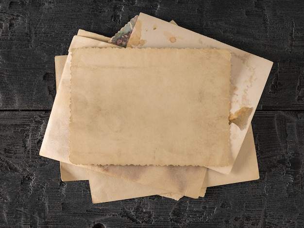 Стопка старых фотографий на черном деревянном столе. предмет семейных ценностей. вид сверху. плоская планировка.