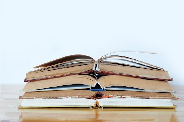 흰색 배경에 있는 나무 탁자에 펼쳐진 책 더미