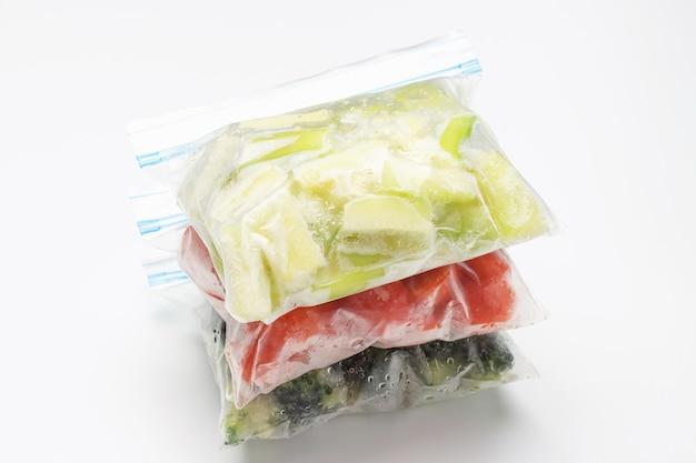 Стек пакетов замороженных овощей на белом фоне крупным планом