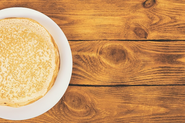 木製のテーブルの上の白いプレート上のパンケーキのスタック。ラベル、レイアウト、モックアップの場所。上面図。