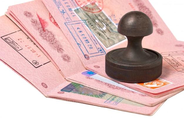 パスポートと白で隔離されるスタンプのスタック