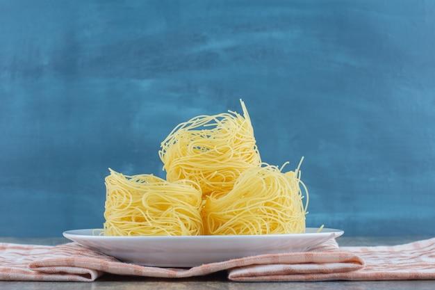 Стопка макарон на тарелке, на полотенце, на мраморной поверхности.