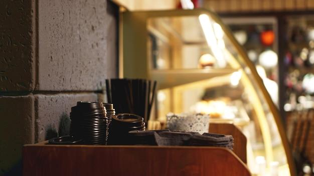 커피용 플라스틱 캡과 튜브 더미. 갈색 톤으로 된 커피숍의 셀프 서비스 공간 - 흐릿한 배경.