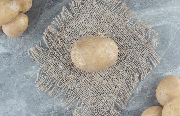 대리석 테이블에 있는 삼발이에 감자 더미.