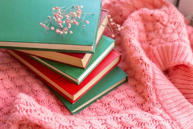 ピンクの暖かいニットセーターにドライフラワーと赤と緑の本のスタック
