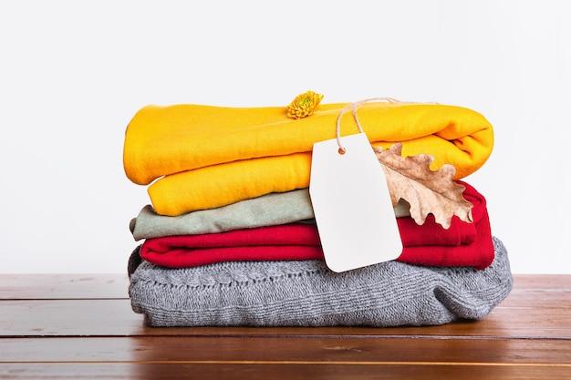 Стопка красных, серых, желтых свитеров осень-зима на деревянном столе и на белом фоне. уютная, теплая одежда.
