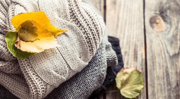 Стопка свитеров и осенние листья