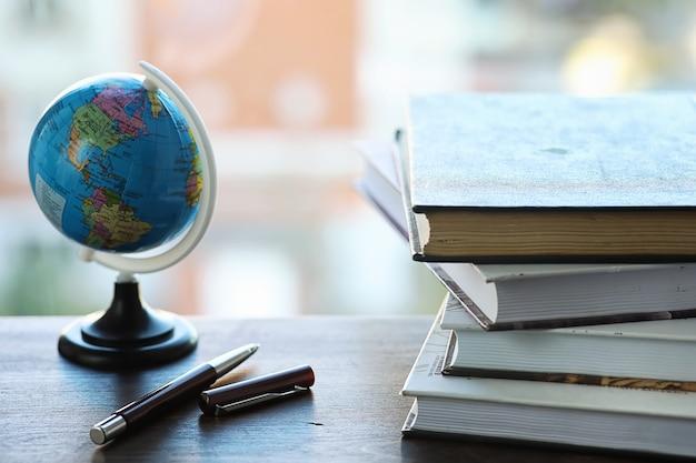 Стопка учебников на подоконнике и письменные принадлежности
