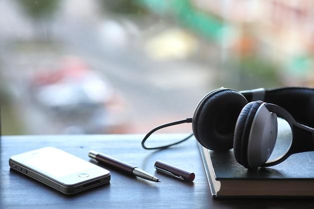 탁자에 검정 헤드폰이 있는 교과서 더미