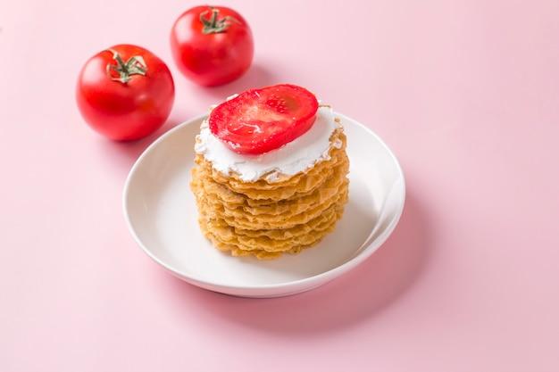 크림 소스와 토마토를 곁들인 얇은 짭짤한 와플 스택