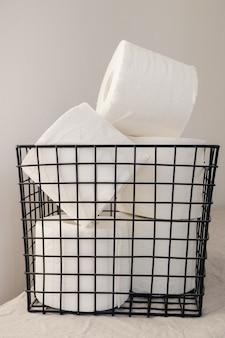 トイレットペーパーのスタックが白い表面に黒い金属製のバスケットにまとめられています。最小限のインテリアデザインコンセプト