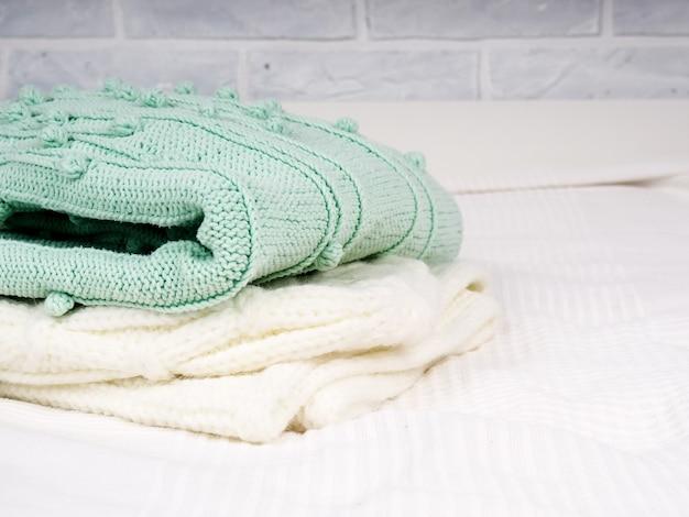 흰색 침대에 따뜻한 니트 물건의 스택. 아늑한 옷. 가정용 개념. 접힌 니트 물건 흰색.