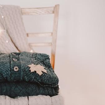 Стопка теплых шерстяных вязаных свитеров и кленовый лист на стуле