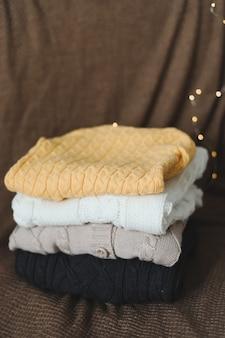 Стопка теплых шерстяных вязаных свитеров на темном фоне
