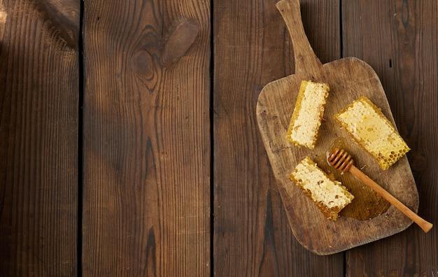 木の板と木のスプーン、茶色のテーブルに蜂蜜とワックスのハニカムのスタック。上面図、コピースペース