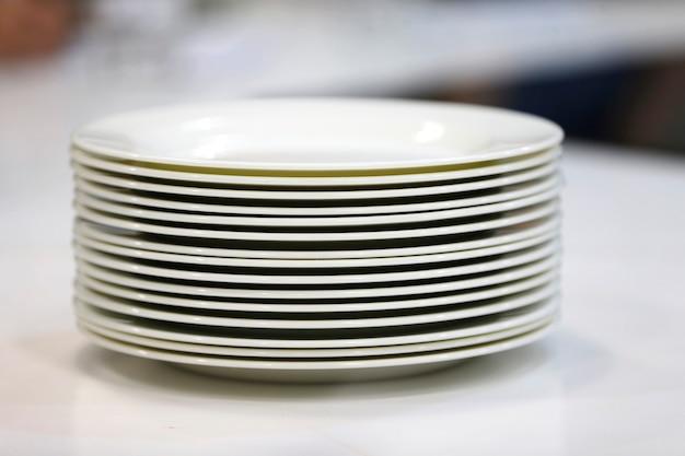 Стопка белых тарелок. множество тарелок. тарелки из ресторана. белые тарелки. тарелки для еды