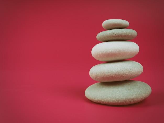 Стопка белых камней дзен на розовом фоне, минимализм.