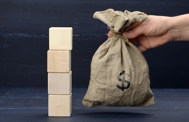 Стопка деревянных кубиков и женская рука держит полную сумку со знаком доллара. концепция сбережений, дотация от государства, накопление средств