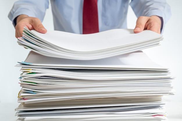 누적 된 문서 또는 보고서 및 그것을 들고 사업가의 손.