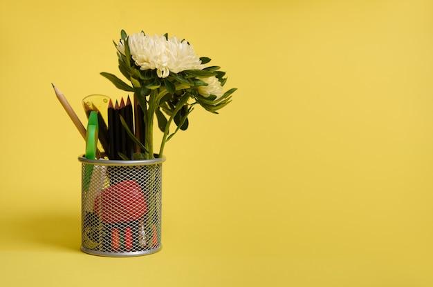 Подставка для ручек и карандашей на рабочем столе на желтом фоне с местом для текста. крупный план металлического ведра с канцелярскими принадлежностями. держатель с цветными школьными принадлежностями и цветком астры