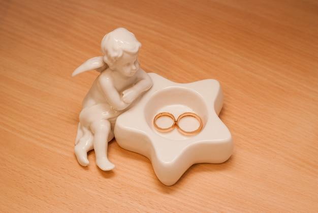 白い天使の小像。ウェディングセット、新郎新婦の結婚指輪。ベージュの背景の静物。