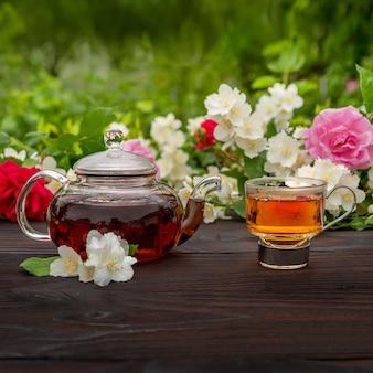 Заварочный чайник и элегантная стеклянная чашка среди цветущих роз и кустов жасмина