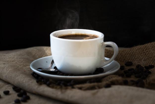ヴィンテージの木製のテーブルにコーヒー豆とコーヒーの蒸しカップ。