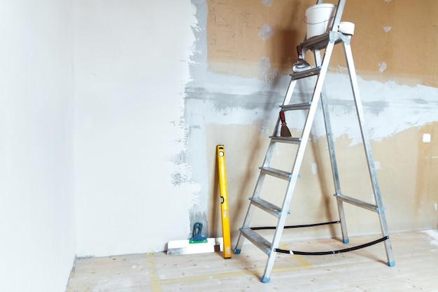 Стремянка с малярными инструментами в комнате в доме или квартире. подготовка к шпаклевке или покраске стены. концепция ремонта или обновления дома.