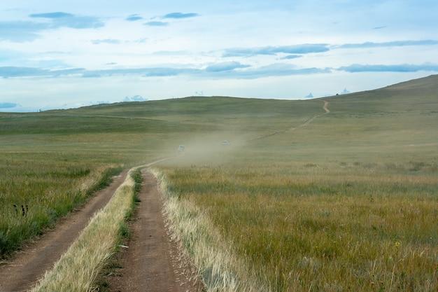 Степь с травой и дорога, по которой в пыли едут две машины. небо с облаками. горизонтальное изображение.