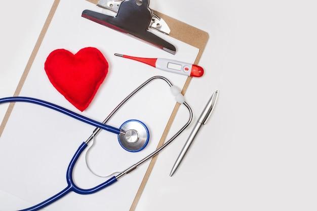 Стетоскоп и термометр в буфер обмена с тканевым красным сердцем