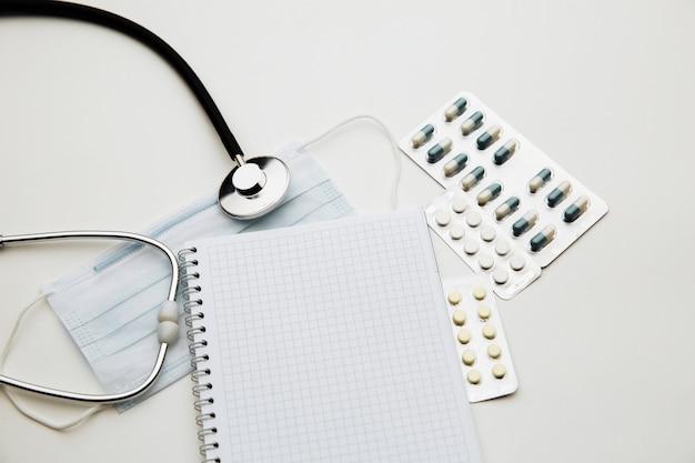 의사 테이블 또는 간호사 책상에 청진기, 안면 마스크, 알약 및 메모장