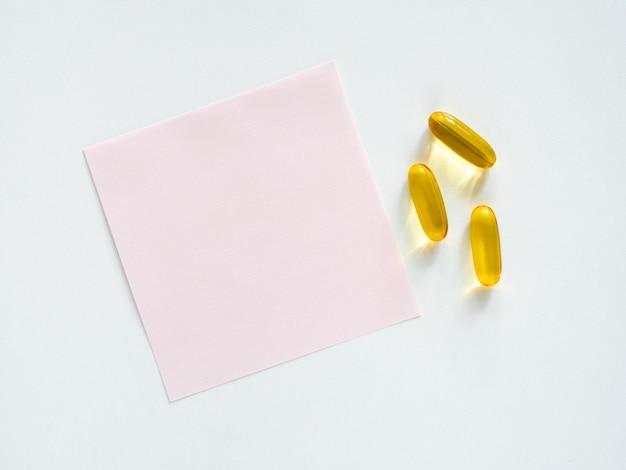Наклейка и горсть таблеток на белом столе, место для копирования, вид сверху, плоская планировка, крупный план