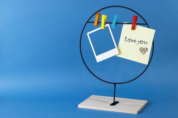 洗濯バサミと青い背景に私はあなたを愛している紙に刻まれたステッカー