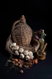 黒の背景にニンニク、タマネギ、エンドウ豆、ナッツの静物