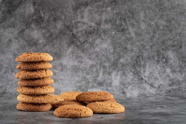 Запас овсяного печенья на сером бетоне.