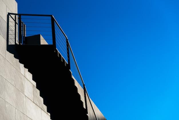 青い空にたくさんのコピースペースがある、モダンなデザインの石の階段。