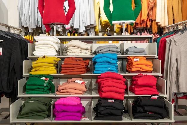 さまざまな色の服がいっぱいの店の棚