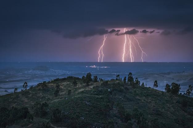 Бурная ночь в поле с молнией на горизонте